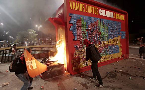 Image from A Folha de São Paulo, 19 June 2013. A protestor sets fire to a World Cup mural